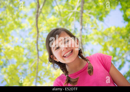 A young girl with braids wearing a pink top under a canopy of trees. - Stock Photo