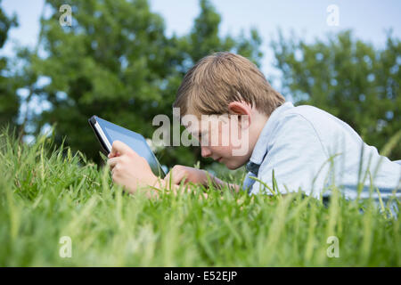 A young boy lying on the grass, using a digital tablet. - Stock Photo
