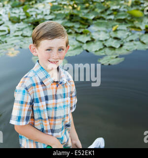 A young boy standing in shallow water with a fishing net. - Stock Photo