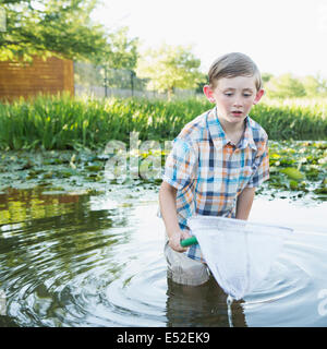 A young boy standing thigh deep in water, with a fishing net. - Stock Photo