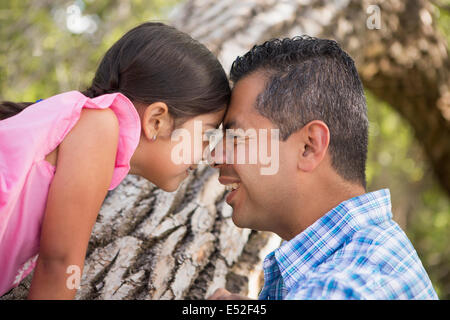 A father and daughter with foreheads pressed together by a tree in the park. - Stock Photo