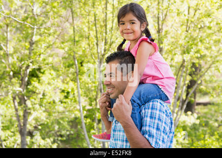 A man giving his daughter a piggyback ride on his shoulders. - Stock Photo