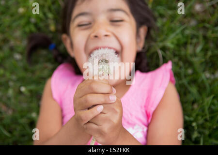 A girl lying on the ground, holding a dandelion seedhead clock. - Stock Photo
