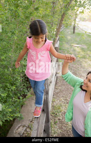A young girl in a pink shirt and jeans, walking along a fence holding her mother's hand. - Stock Photo