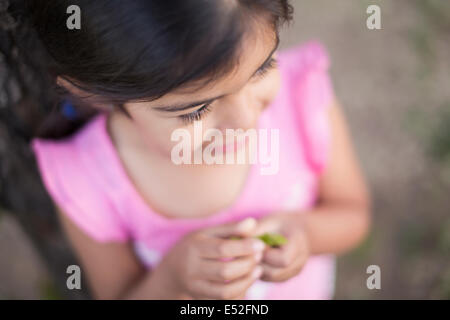 View from above of a child, a girl with dark brown hair and brown eyes. - Stock Photo
