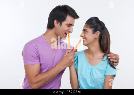 Happy young couple feeding each other orange ice lollies over white background - Stock Photo