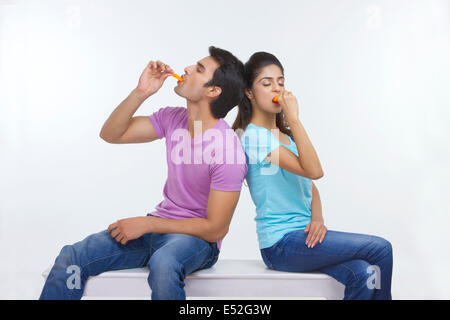 Young couple eating ice lollies while sitting on bench over white background - Stock Photo
