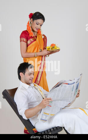 South Indian woman with a thali reading an article in a newspaper - Stock Photo