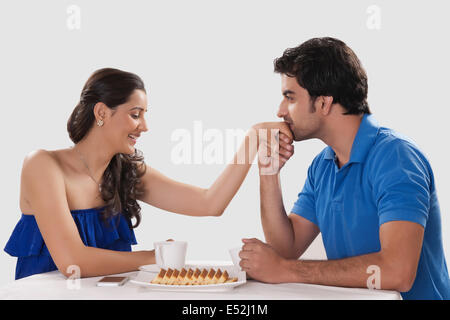 Loving man kissing woman on hand while having coffee against white background - Stock Photo