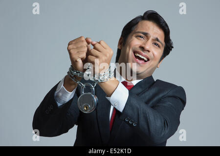 Pleading businessman tied in chain over gray background - Stock Photo