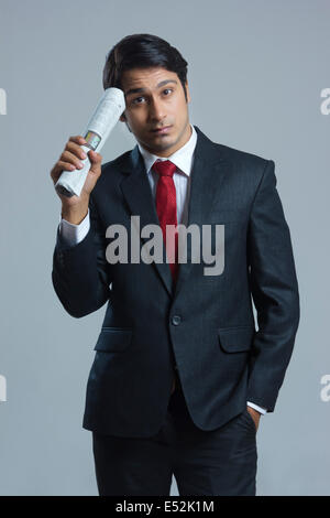 Portrait of confused businessman holding newspaper over gray background - Stock Photo