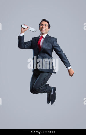 Full length of successful businessman with newspaper jumping over gray background - Stock Photo