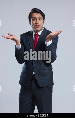 Portrait of confused businessman gesturing against gray background - Stock Photo
