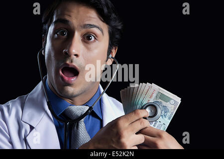 Portrait of shocked male doctor examining Indian currency with stethoscope against black background - Stock Photo