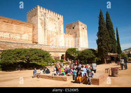Fortified walls of the Alcazaba castle in the Alhambra complex, Granada, Spain with a group of school children in - Stock Photo