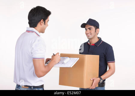 Man signing for package from delivery man against white background - Stock Photo