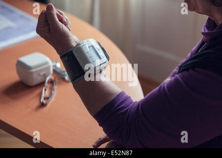 Elderly woman checking her blood pressure at home - Stock Photo