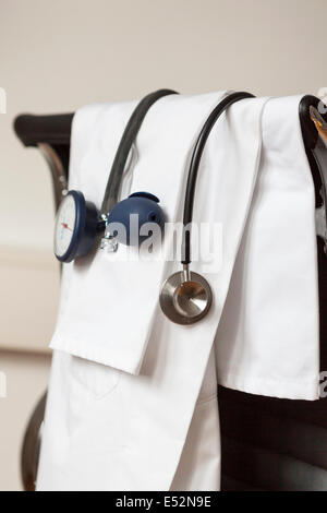 Stethoscope,blood pressure monitor and white coat in doctors office - Stock Photo