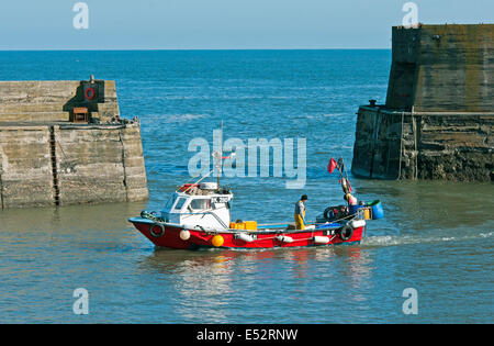 Fishing or Crabbing Boat returning to Craster Harbour on the Northumberland Coast after being out fishing - Stock Photo