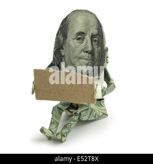 Origami human figure made of U.S. paper currency sitting with a blank cardboard sign held in front of him as if - Stock Photo
