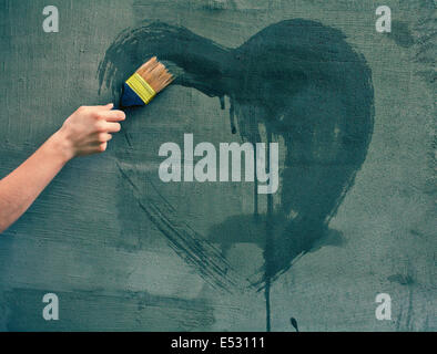 Female hand painting heart on the concrete wall - Stock Photo