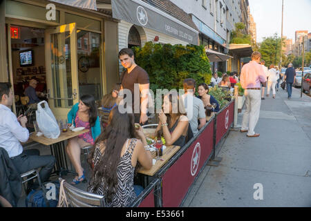 groups of young people enjoy al fresco late afternoon happy hour at sidewalk tables on West 14th street in Chelsea - Stock Photo