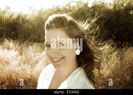 A model walks through a field during the golden hour while wind blows through her hair. - Stock Photo