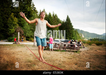 A man walks a slack line at sunset.  Life along the Stawamus Chief Provincial Park campsite, also known as the Squamish - Stock Photo