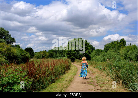 Views around the Flatford Mill area which were made famous by the paintings of John Constable - Woman walking down - Stock Photo