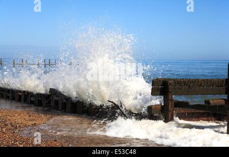 Waves breaking against old sea defences at Cart Gap, near Happisburgh, Norfolk, England, United Kingdom. - Stock Photo
