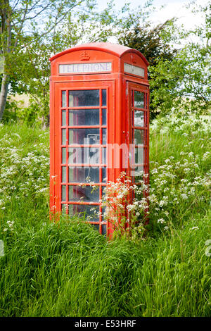 Traditional red telephone box in rural area becoming overgrown through lack of use, Wiltshire, England - Stock Photo