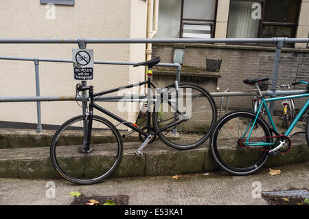 Bicycles locked to railings next to a notice bicycles will be removed, it in Trinity College Dublin, Ireland - Stock Photo