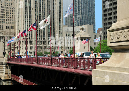 People crossing the DuSable bridge over the Chicago River. - Stock Photo