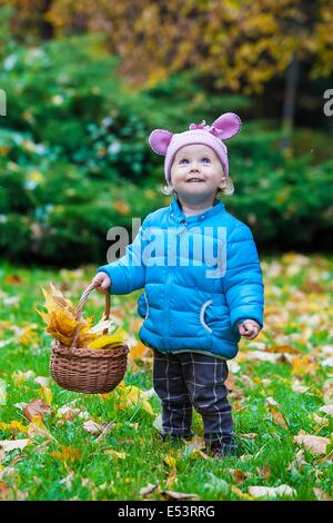 Laughing kid standing in an autumn park