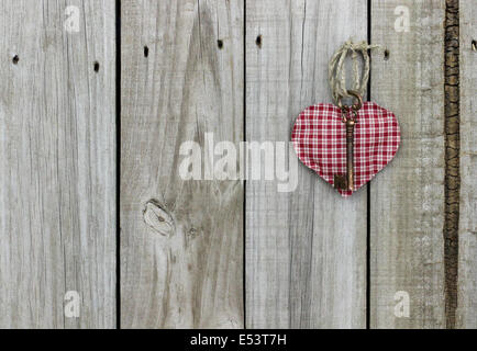 Key to my heart; red checkered (plaid) heart with brass skeleton key hanging on rustic wooden door - Stock Photo