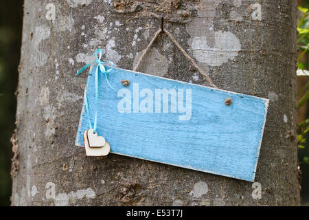 Blank rustic blue sign with hearts hanging on tree in forest - Stock Photo