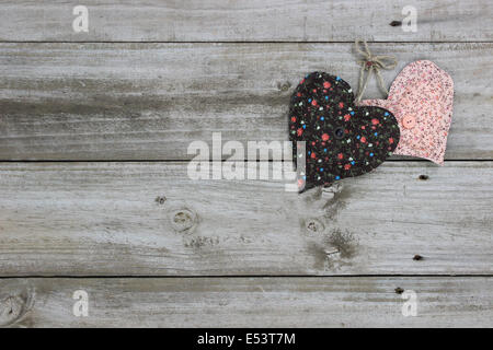 Brown and peach calico country hearts hanging on rustic wooden background - Stock Photo
