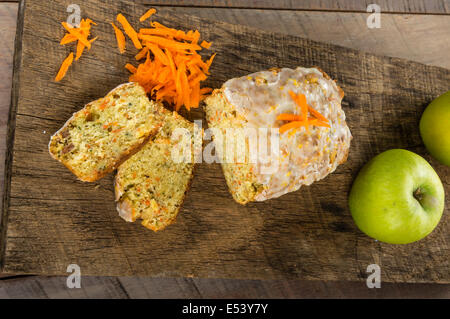 Carrot apple cake on wooden table with shredded carrots - Stock Photo