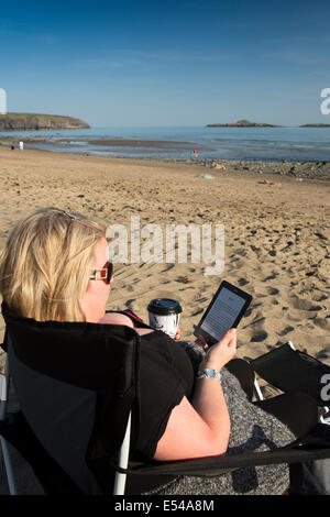 UK, Wales, Gwynedd, Lleyn peninsula, Aberdaron, beach, woman relaxing reading book on ereader drinking coffee in - Stock Photo