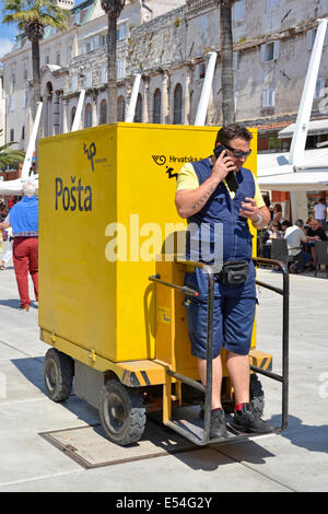 Postman making a phone call whilst stationary on an unusual Posta delivery vehicle in Split town centre postal service - Stock Photo