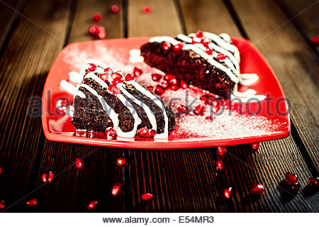 Christmas chocolate cake dessert with pomegranate grains on red plate - Stock Photo