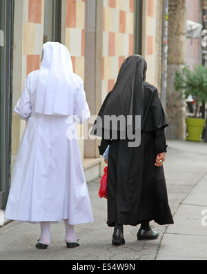 two old sisters with black suit and white dress walking in town - Stock Photo