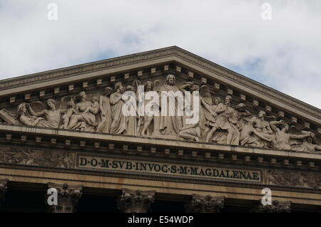 Roof apex of L'eglise de la Madeleine church in Paris against a bright cloudy sky showing exterior architectural - Stock Photo