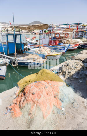 Colourful fIshing boats and nets piled on quayside in the Aegean port of Kusadasi, Turkey on a sunny summer day - Stock Photo