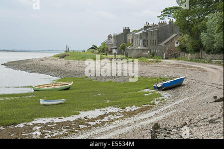 View of boats on shoreline and houses of coastal village, only community on U.K. mainland dependent upon tidal access, - Stock Photo