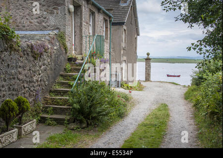 Houses in coastal village and river, only community on U.K. mainland dependent upon tidal access, with vehicular - Stock Photo