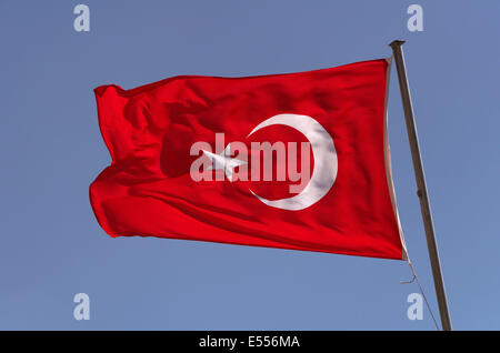 Turkish Flag with crescent and star against blue sky - Stock Photo