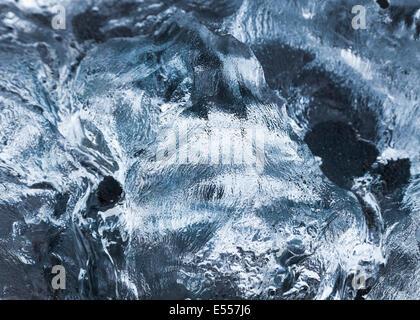 Close up of melting ice piece on the black sand beach near Jokulsarlon, Southeast Iceland - Stock Photo