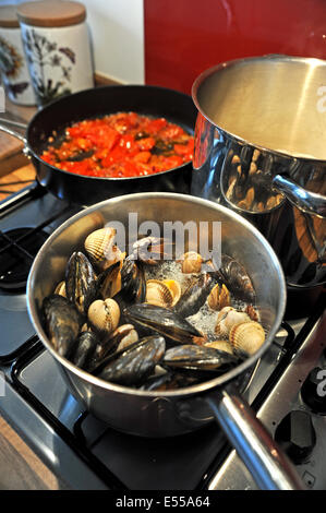 Seafood of mussels clams prawns and cockles with linguine pasta cooking  The shells open to show they are cooked - Stock Photo