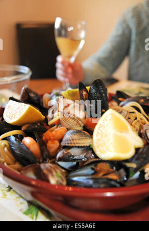 Seafood of mussels clams prawns and cockles with linguine pasta and a fresh tomato sauce . Italian food - Stock Photo